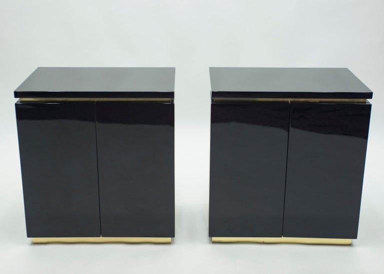 Glossy black lacquer, paired with bright brass accents, feels crisp and luxe on this pair of small cabinets. Their boxy, simple style is typical of both the 1970s and designer Jean Claude Mahey for Maison Romeo design. Whether used as two small