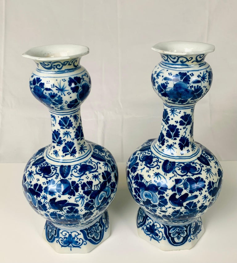 This pair of blue and white Dutch Delft vases was hand-painted in cobalt blue. The exquisite blue decoration features an all-around scene in the