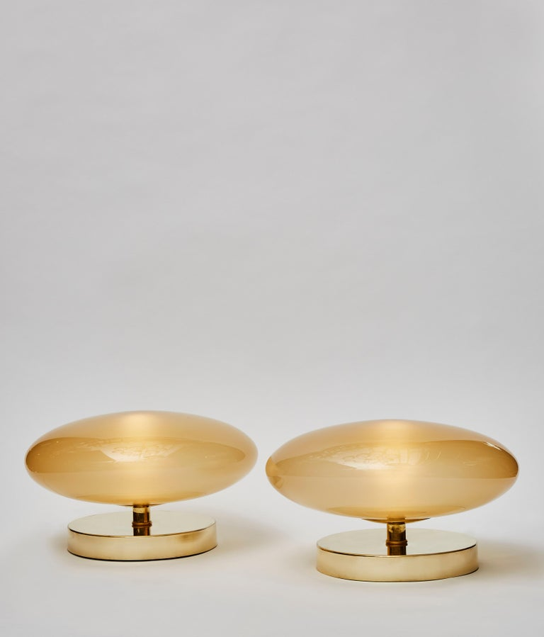 Pair of small table lamps, made of brass feet and wide tinted glass globe.