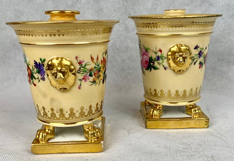 Pair of hand painted small bough pots by Darte Frères Paris, France. The tops have everted rims while the body with lion's paw feet rest on a square base. The side handles are lion's heads. There is slight ware to the burnished gold due to the age