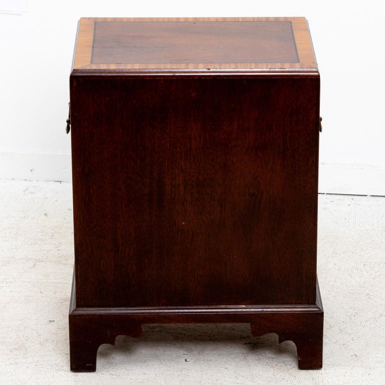 Pair of small size mahogany three-tier chest of drawers featured with metal handles on the drawer fronts, light wood accent trim, and bracket feet. The chests also come with metal handles on the sides for transport. Please note of wear consistent