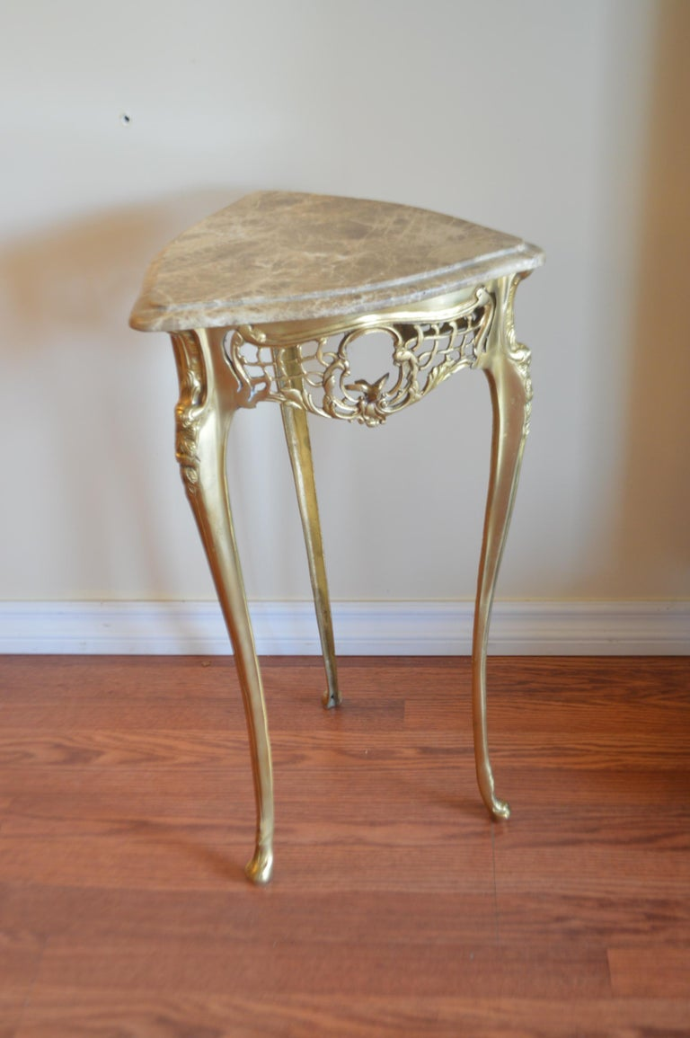 Most unusual pair of small side tables, triangle shape with attractive marble tops. The gilded bronze base is highly decorative with a lace design apron holding a small bird on each side of the table. The legs are fine and elegant. The type of