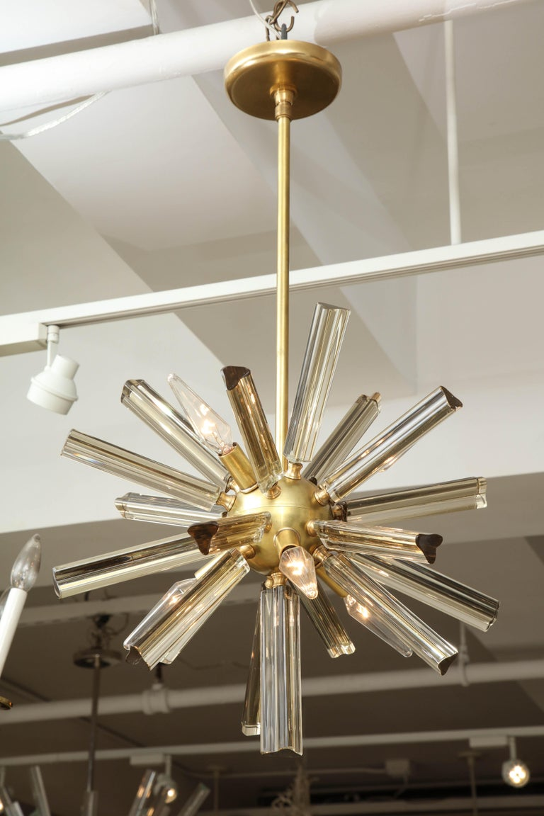 A pair of small Sputnik chandeliers with a brass frame and slightly smoky glass. Re-wired for use in the U.S. and ready to hang.