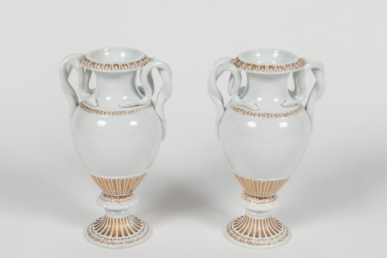 Stylish and chic pair of Meissen urns in Classic glazed white porcelain with gold accents. These urns are classical in form and feature entwined snakes as handles. A timeless design that works well in both Classic and contemporary interiors. The