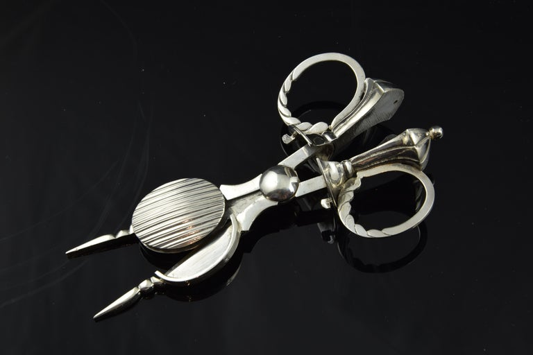The handle has been worked giving it the shape of a vase, with the lobed handles in its lower area to remember cloth draperies, while the peak of the snuffers has a needle with pearl and the oval area a decoration of grooves. All these elements, and