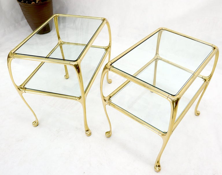 Pair of forged solid brass end side tables with glass tops.