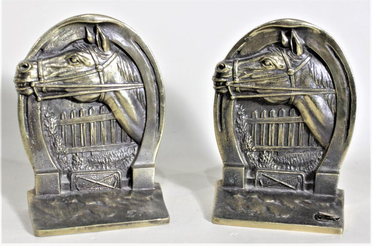This pair of solid cast brass bookends was made by the Hohn manufacturing company of New Hampshire in approximately 1970. The bookends depict a silhouette of a horse's head with a picket fence in the background and bordered on the top by a horse