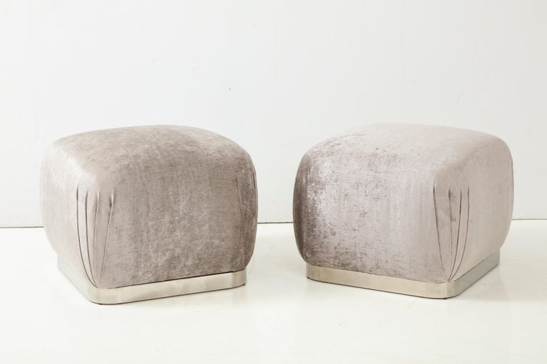 Pair of Souffle ottomans or poufs by Karl Springer. The ottomans have been newly reupholstered in a beautiful silvery grey Romo velvet fabric, and they sit on polished steel bases.