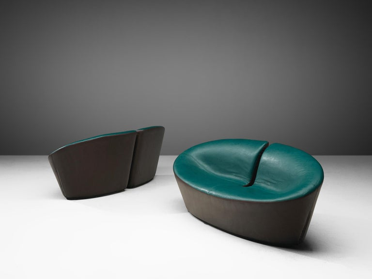 Pair of sofas, leatherette, France, 1970s  A set of Space Age settees with a distinctive design. An oval, disk shaped seat with a notch in the middle that runs all the way down. This gives a wonderful effect from the back and makes it an interesting