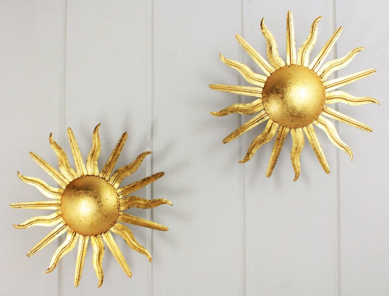 Pair of hand-hammered iron sunburst ceiling light fixtures with gold leaf finish. Spain, 1950s.  These sunburst ceiling sconces have curved and straight alternating rays surrounding a central sphere, On sale as a pair.  Available a huge