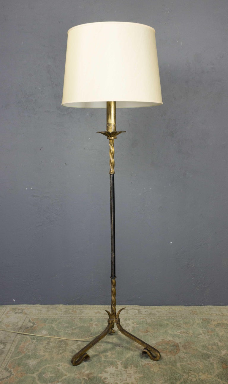 A pair of gilt iron floor lamps with a wrapped leather stems. Shades not included, Spanish, 1950s.