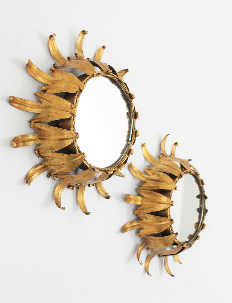 Beautiful pair of hand-hammered gilt iron leafed sunburst mirrors in small size. Spain, 1950s. Lovely to place together or as a wall composition with other sunburst mirrors in different sizes to add a Hollywood Regency taste to any room. Overall