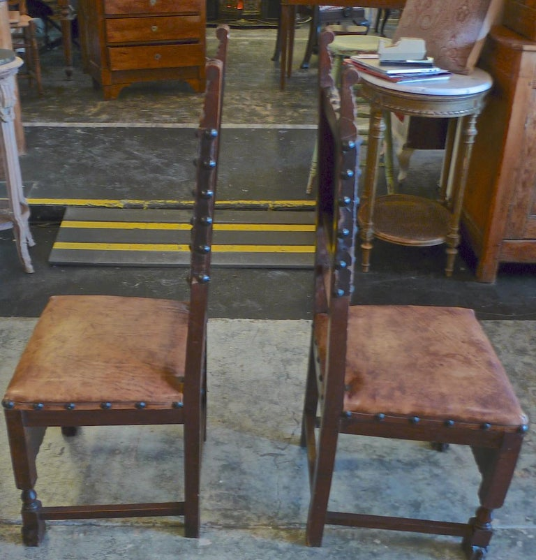 Pair of Spanish 18th century high back studded leather dining chairs.