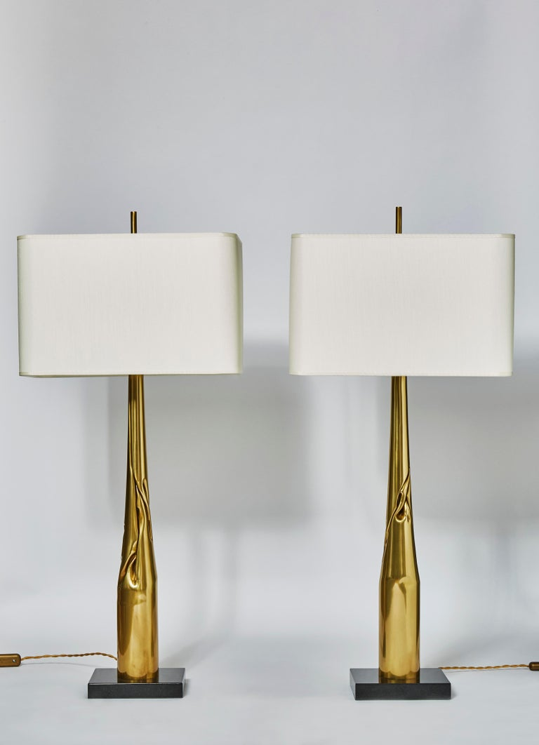 Pair of table lamps made of square black marble bases and twisted and folded brass bodies.  Each lamp is unique, made by the edition house Esperia exclusively for Glustin Luminaires.