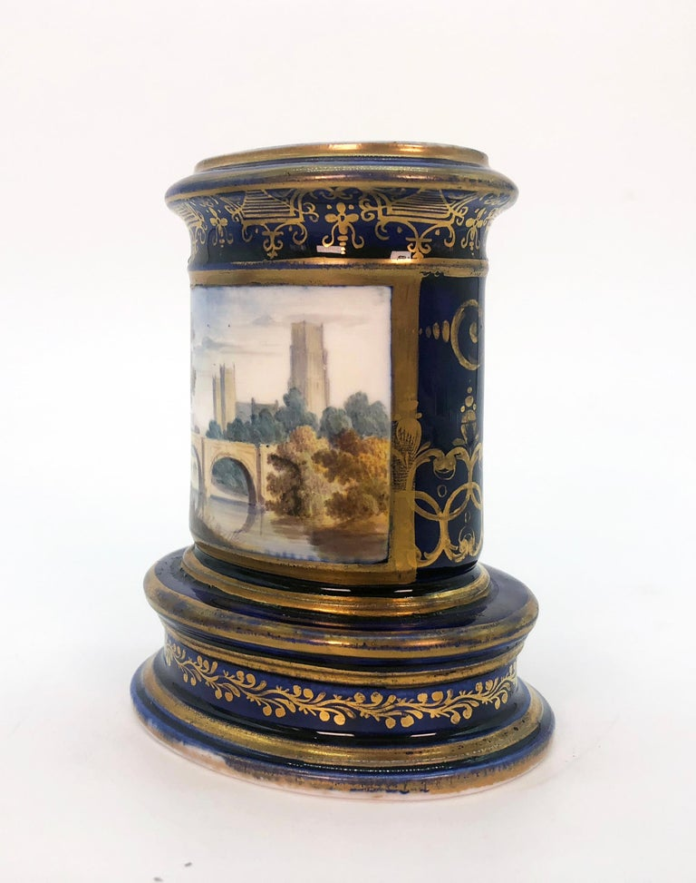 Pair of Spode spill vases, circa 1820. Cobalt blue and gilt with finely painted scenic panels, both depicting Cathedral City views. Marked to bases 'Durham/Spode' and 'The Cathedral and port of the city of Hereford/Spode' respectively. A spill vase