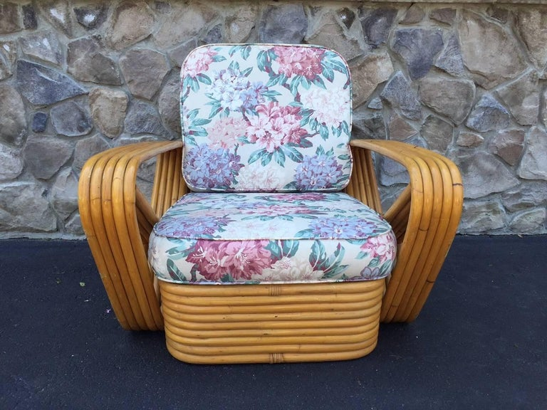 Pair of square pretzel rattan lounge chairs in the style of Paul Frankl. The chairs have a stacked rattan base with original cushions. Measures: 31 W x 37.5 D x 31 H (to top of back cushion).