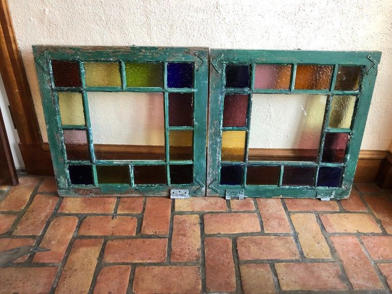 Pair of stained glass windows. Bright and colorful these would add to any interior or exterior project. The colors include cobalt blue , amber, yellow ,green and purple all around the edges and clear white in the middle. These windows also have the