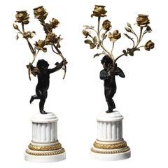 Pair of Standing Cherub Patinated Bronze and Gilt-Bronze Figural Candelabrum