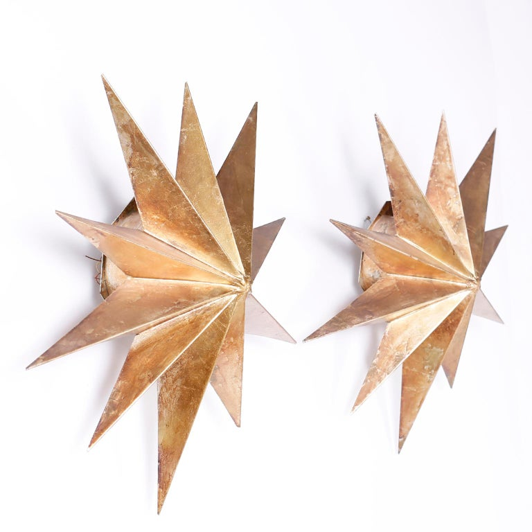 Pair of midcentury star form wall sconces with ten points, each crafted in aluminum with a gold leaf finish and spray lighting from behind. Newly wired.
