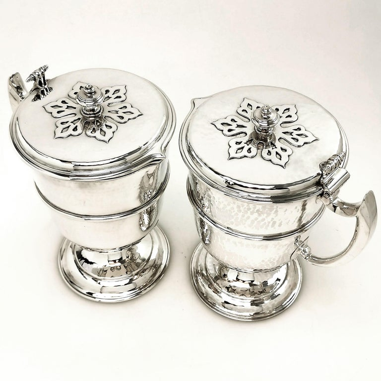 A gorgeous pair of Antique Solid Silver Jugs created in the style of William and Mary late 17th century style. Each Jug has a hinged lid with an applied pattern on the lid. The bodies feature a delicate hammered effect and each jug stands on spread