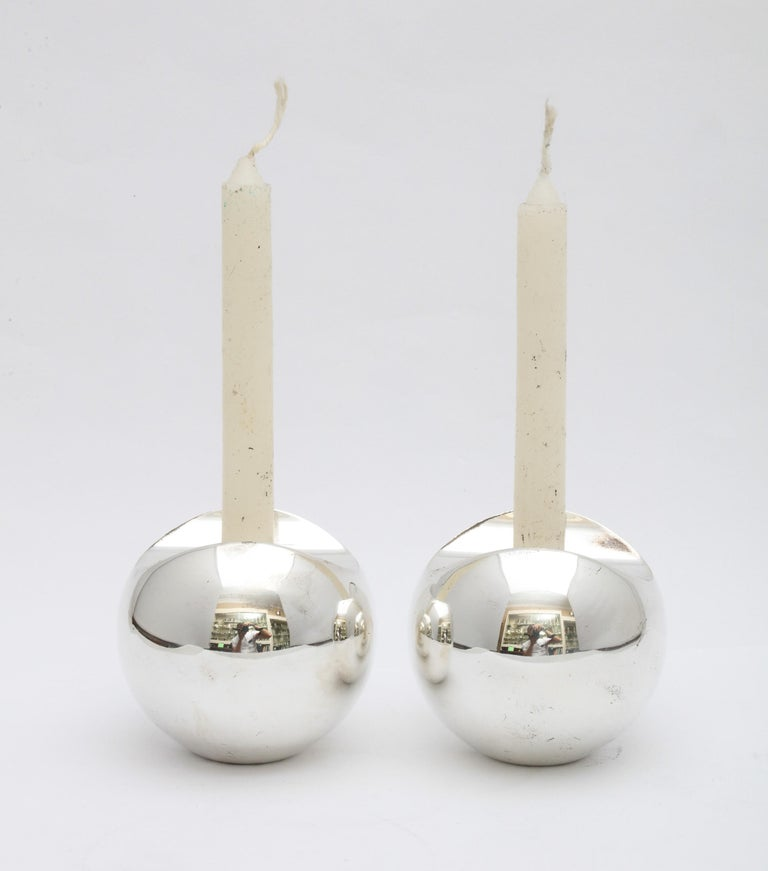 Pair of Mid-Century Modern, sterling silver candlesticks, hallmarked for Stockholm, Sweden, circa 1950s, Timo Sarpeneva, maker. Each candlestick measures 2 1/4 inches high x 2 1/2 inches diameter. Weighted. Dark spots in photos are reflections.
