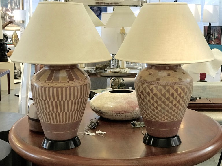 A wonderful large scale Native American (Acoma?) pots made into impressive large lamp, by the re-known interior designer Steve Chase. They are a mated pair as they are painted slightly differently. Steve Chase was well known for using old and
