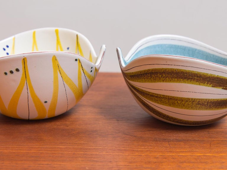 Pair of original faience leaf bowls by Swedish designer Stig Lindberg for Gustavsberg. These playfully formed bowls have undulating, asymmetrical walls with hand painted features. The loose, geometric designs wrap around and inside the white glazed