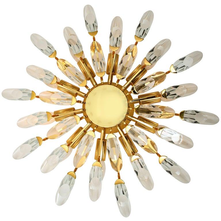 High-end gilded brass flush mounts by Stilkronen, made in Italy, circa 1975. Each fixture is featuring a sunburst array of branches holding 30 clear crystals pieces. The crystals refract light beautifully and are perfect for a soft, warm and