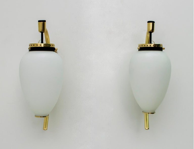 Pair of sconces in polished brass, black lacquered metal and opal glass. Produced by Stilnovo in Italy in the 1950s. The sconces have been completely restored and polished.
