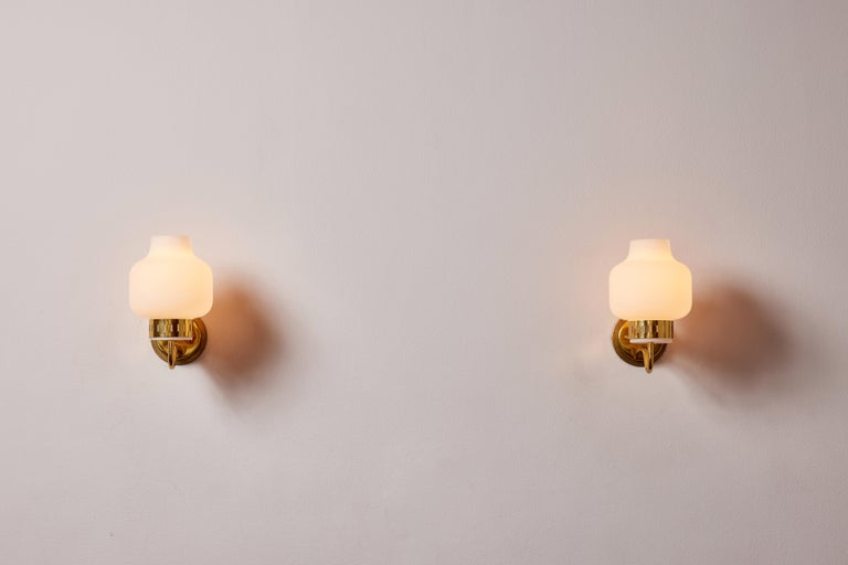 Pair of Stilnovo sconces. Manufactured in Italy, circa 1950's. Brushed satin glass diffusers, brass, custom brass backplates. Rewired for U.S. standards. We recommend one E27 60w maximum bulbs per fixture. Bulbs provided as a one time courtesy.