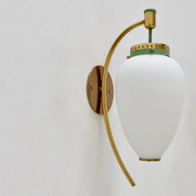 Vintage pair of Italian Stilnovo sconces from the 1950s. In naturally aged brass and glass. Naturally aged. Single E12 candelabra based socket per sconce. Priced as a pair. Wired for use in the US. Lightbulbs included with