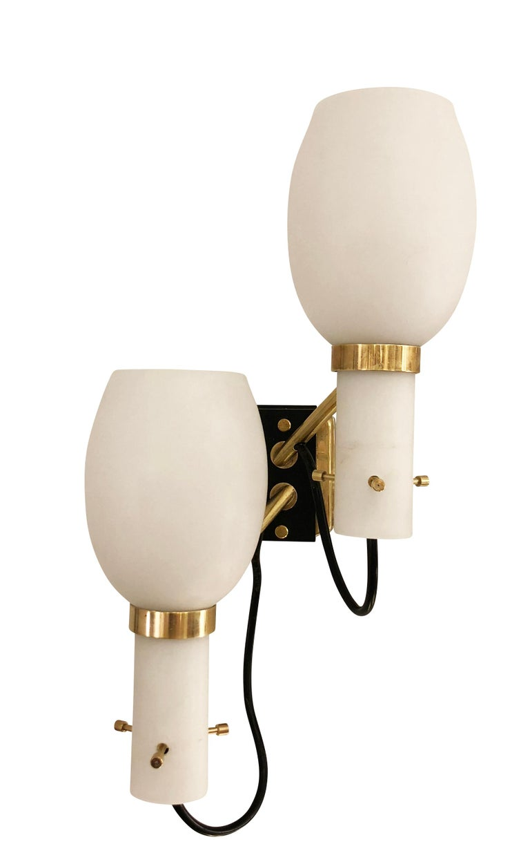 Pair of midcentury Italian wall lights by Stilnovo with staggered frosted glass shades. Brass and black lacquered hardware. Two candelabra sockets per sconce.  Condition: Excellent vintage condition, minor wear consistent with age and