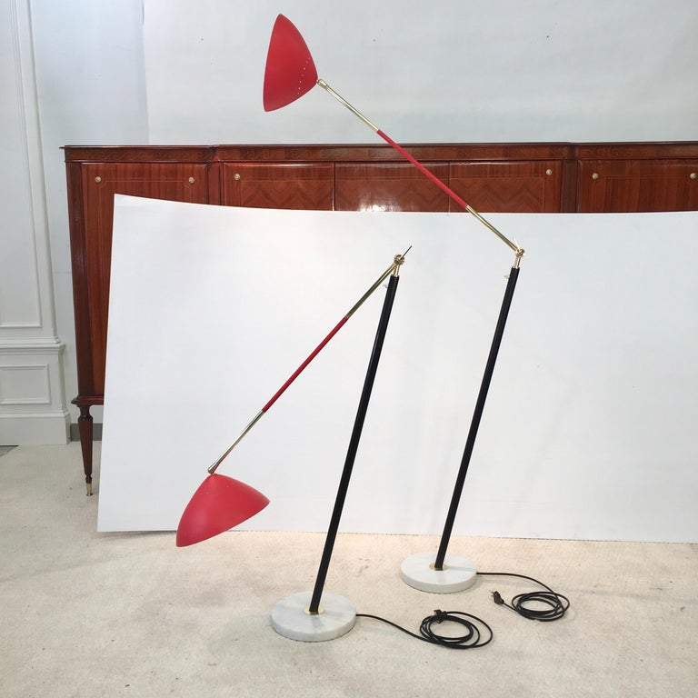 Matched pair of floor lamps by Stilux Milano designed by Oscar Torlasco with red shades, black enameled metal stem, brass arms and mounts. Articulating stem and shade with a white round marble base. Push button switch on stem. Iconic and playfully