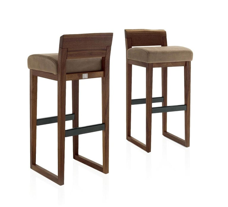 Handcrafted set of 2 bar or counter stools, characterized by a structure in solid American walnut and backrest with a natural edge. Upholstered seat in Italian Utah leather.