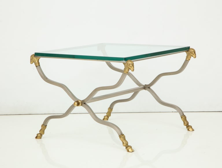 Pair of brass and glass end tables with ram's head finials and ram's feet.