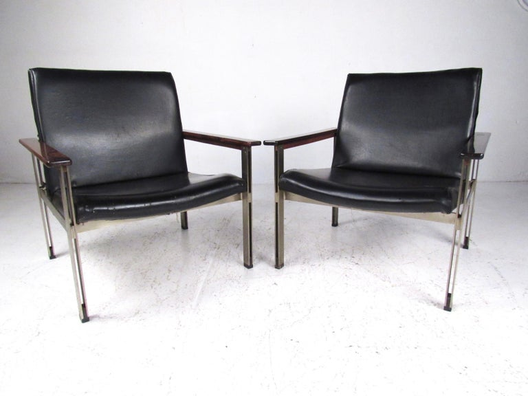 This stylish pair of matching lounge chairs features midcentury Italian modern design with Rosewood armrests and metal base frames. With eye-catching style and uniquely shaped seat backs, this vintage pair of armchairs make a distinguished yet