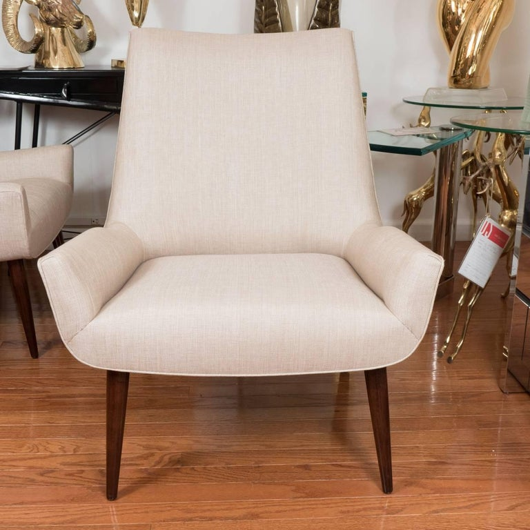 Pair of low, stylized armchairs with tapered mahogany finish feet.