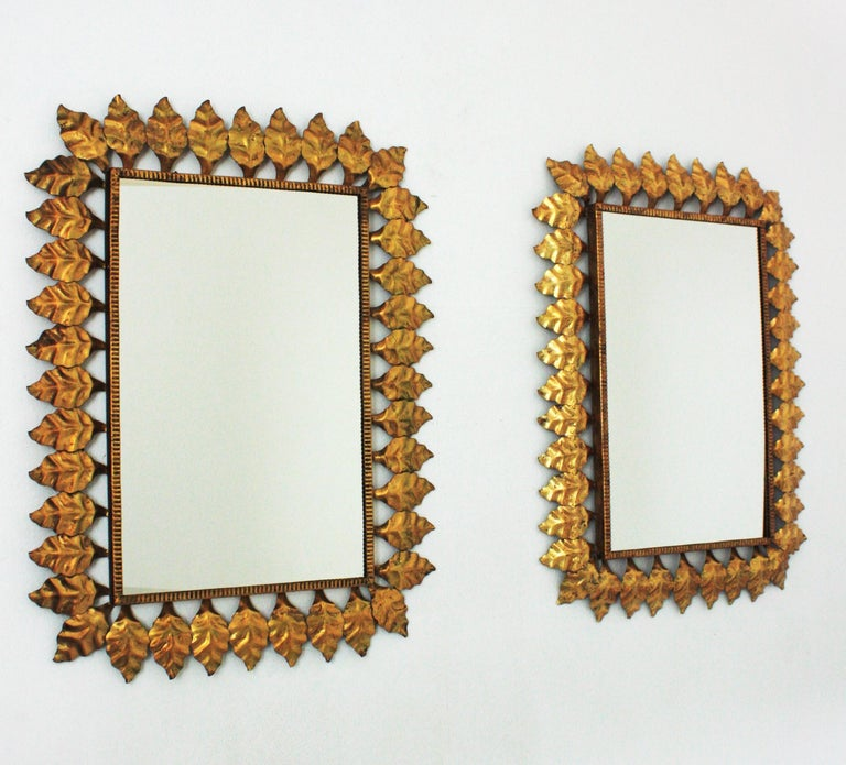 Pair of hand-hammered iron sunburst rectangular wall mirrors with gold leaf finish, Spain, 1950s. Highly decorative rectangular leaf framed sunburst mirrors with gold leaf gilding and large glass surfaces. They have a nice aged patina showing