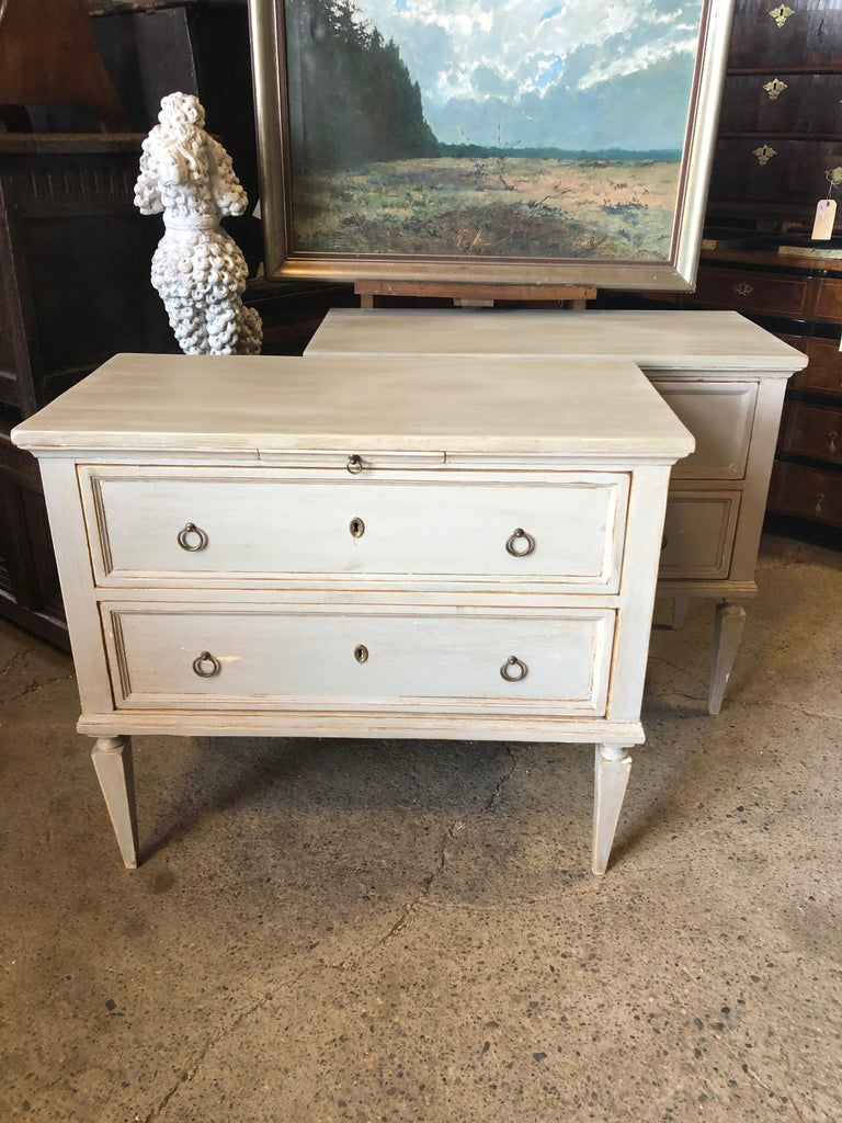 A pair of antique Swedish Gustavian painted wood chests from the early 19th century, with beautiful classic long tapered fluted legs, original hardware and original pull-out writing shelves. Lovely Swedish Blue Gray distressed paint finish. Born in