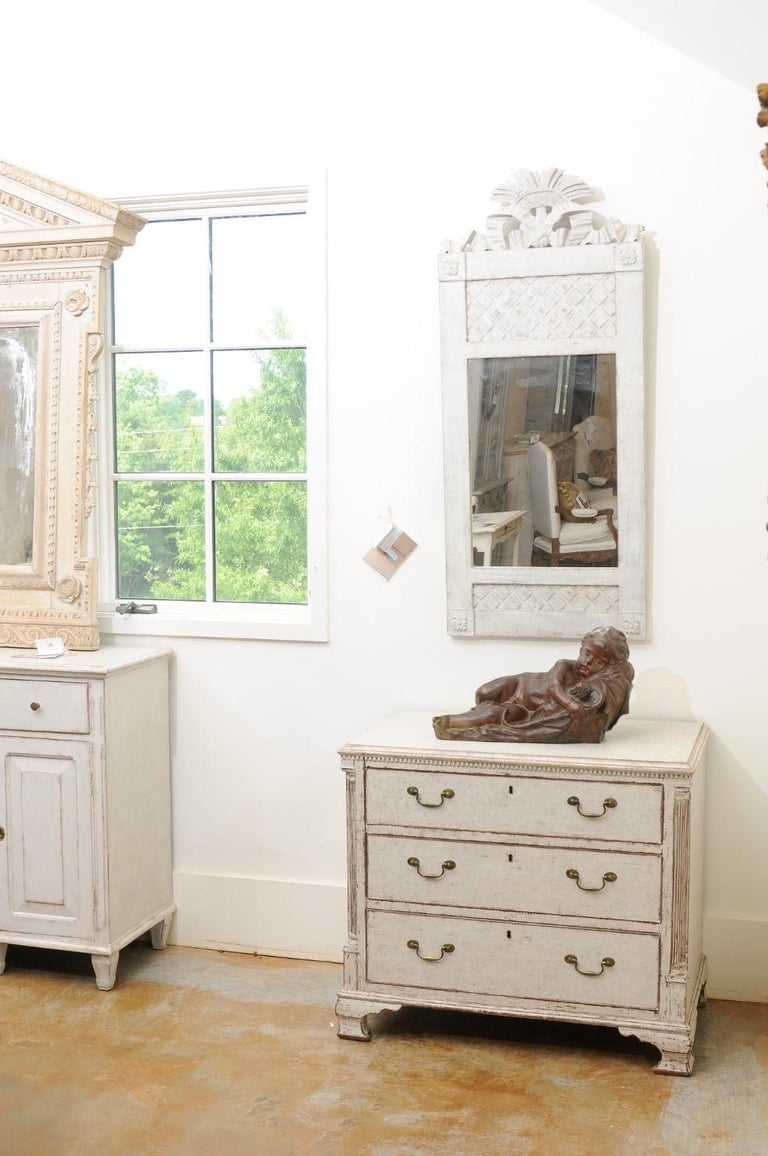 A pair of Swedish painted three-drawer chests from the 19th century, with dentil moldings, fluted semi columns and bracket feet. Born in Sweden during the 19th century, each of this pair of chests features a slightly raised rectangular top, sitting