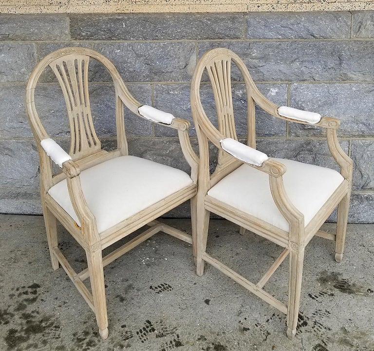Pair of period Gustavian armchairs, Sweden circa 1800, with rounded backs and upholstered seats. The pierced splats and top rails have carvings of wheat, a symbol of prosperity and abundance. Padded armrests, square legs, and H-shaped stretchers. No