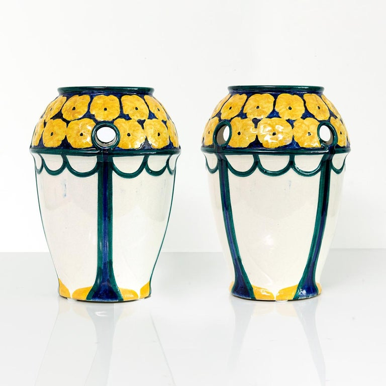 """Pair of Swedish Art Nouveau period vases with a crown of yellow flowers on a deep blue ground. The vases has small round openings along the top. Designed by Alf Wallander made by Rorstrand, circa 1910.   Measures: Height 10.75""""."""