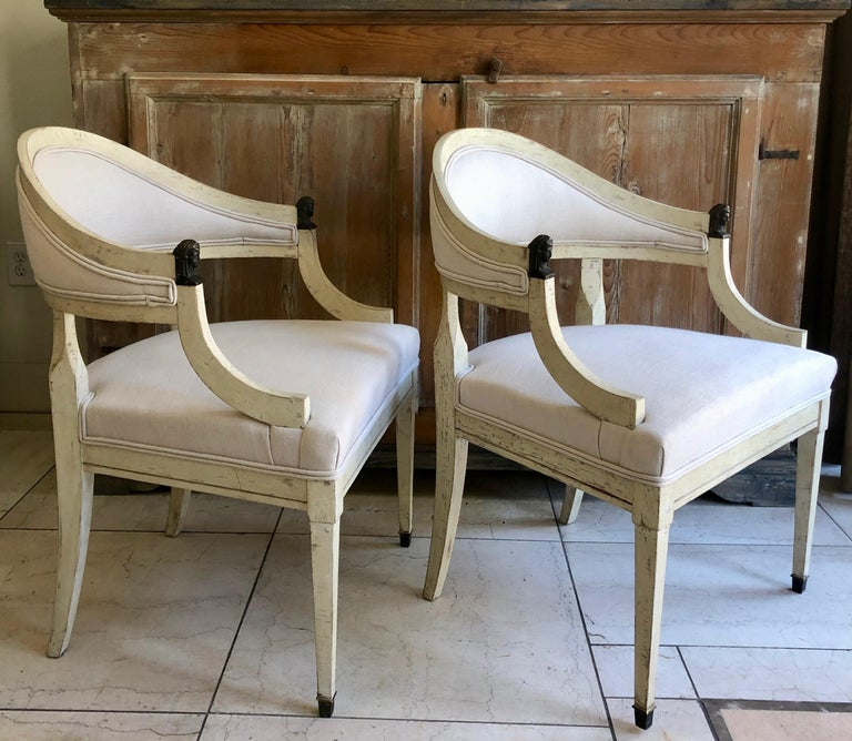 Pair of barrel back chairs, Sweden circa 1890, with rounded form, bronze figural pharaoh head details on handrest and slender tapered legs with bronze fittings. Original worn cream/ white paint finish and new linen upholstery.