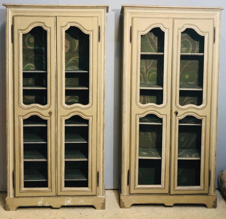 Pair of continental bookcase cabinets. Painted in an olive green with white and gray design this magnificent pair of bookcase cabinets are simply worthy of any home setting. The pair sit in their original splendor with a fully painted interior and