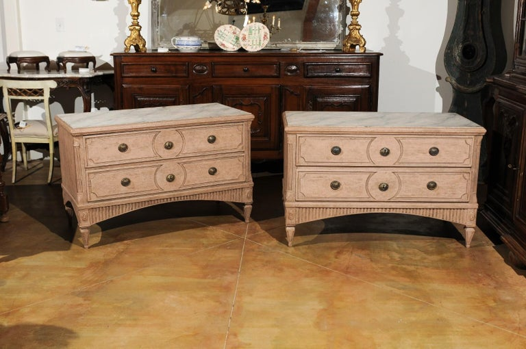 A pair of Swedish Gustavian period two-drawer painted chests from the late 18th century, with marbleized tops, fluted accents and soft pink color. Each of this pair of Swedish Gustavian commodes features a rectangular top with faux-marble inset,