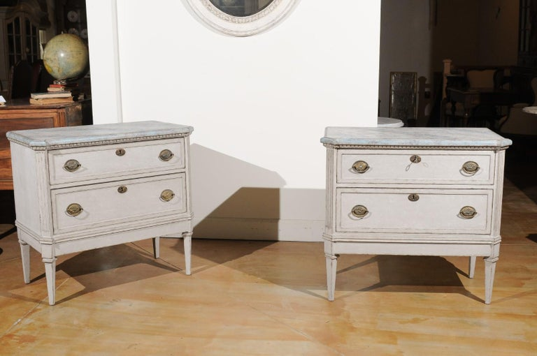 A pair of Swedish Gustavian style painted two-drawer chests from the 19th century, with marbleized tops and fluted motifs. Created in Sweden during the 19th century, each of this pair of Gustavian style chests features a faux marble painted top with