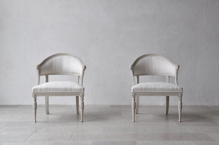 A Swedish Gustavian style pair of antique klismos armchairs. These stunning chairs have barrel backs with cravings of lions' heads. The seat frame features beautiful carving detail and the corner posts are adorned with rosettes. This pair has been