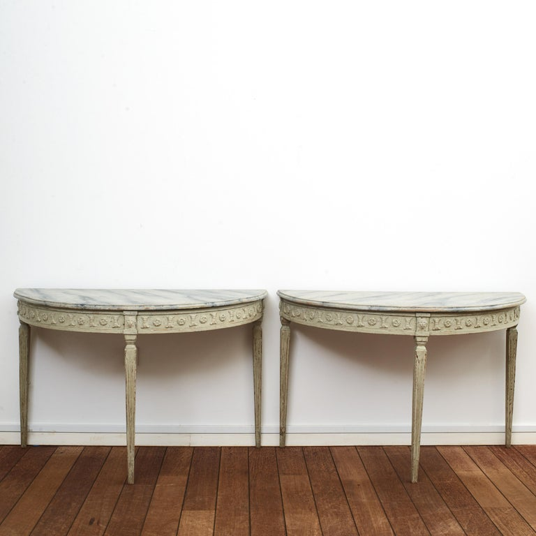 Pair of Swedish demilune Gustavian style console tables on tapered fluted legs.