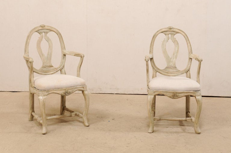 A pair of Swedish Gustavian carved-wood armchairs from the early 19th century. This splendid pair of antique 'Svenska Modellen' (meaning Swedish Model) armchairs from Sweden feature the open, rounded framed backs with wavy, pierced splat-back,