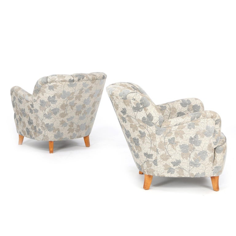 Swedish furniture design: A pair of comfortable easy chairs with channelled backs, legs of birch. Seat, sides and back upholstered with flowered grey wool. Manufactured by 1940s-1950s. There is a matching sofa.